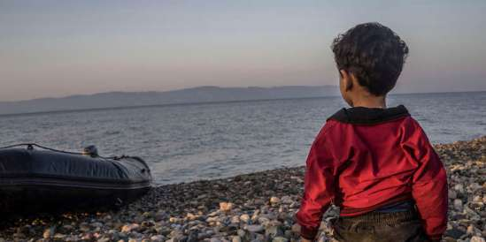 A young boy looks out to sea from the shores of the Greek islan